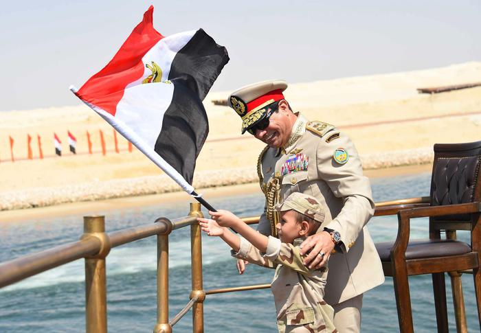 In this picture provided by the office of the Egyptian Presidency, Egyptian President Abdel-Fattah el-Sissi smiles at a boy dressed on a tiny military uniform as he waves the national flag from a monarchy-era yacht that sailed to the venue of a ceremony unveiling a major extension of the Suez Canal in Ismailia, Egypt, Thursday, Aug. 6, 2015. El-Sissi has billed the extension as an historic achievement needed to boost the countrys ailing economy after years of unrest. (Egyptian Presidency via AP) MANDATORY CREDIT
